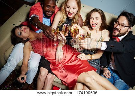Two multiethnic couples clinking glasses together while sitting on couch, their drunken attractive female friend with champagne bottle in hand lying on their laps