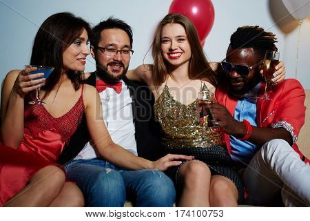 Two cheerful male and two female friends sitting next to each other on couch and having fun together in living room