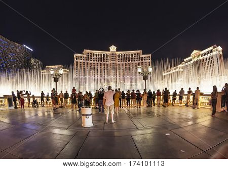 People Watch Famous Bellagio Hotel With Water Games In Las Vegas At Night