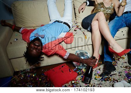 Unrecognizable couple sitting on sofa while Afro-American man lying upside-down with closed eyes and holding champagne bottle in hand