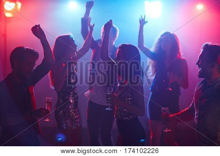 Happy students celebrating prom in night club, dancing with raised hands and holding glasses of champagne