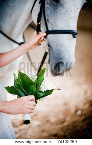 the bride holding a bouquet in hand and side by side and the horse