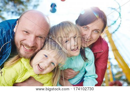Waist-up portrait of happy family of four taking pleasure in spending sunny day together in funfair, lens flare