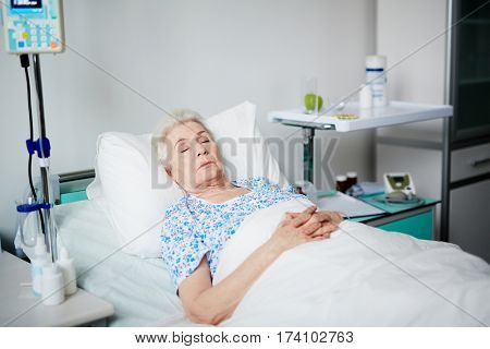 Senior woman asleep on bed after getting her treatment in geriayric hospital