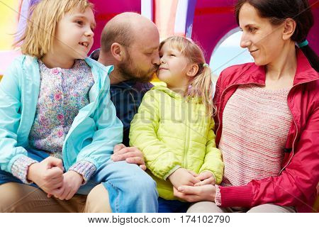 Lovely family portrait: bearded father kissing gently his little daughter in cheek while holding her elder sister on laps, their smiling beautiful mother looking at them