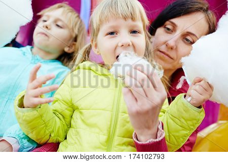 Waist-up portrait of two blond-haired little girls eating delicious cotton candy while their middle-aged mother holding one of them on laps