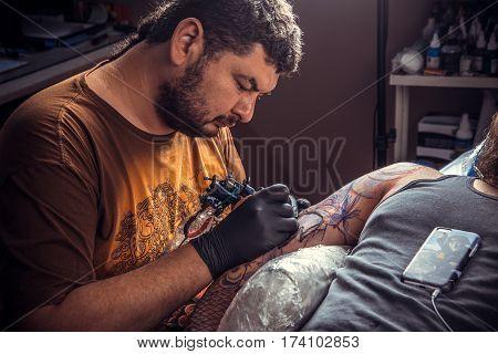 Tattoo specialist posing in salon/Tattoo master making a tattoo in studio.