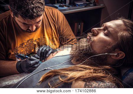 Professional tattoo artist makes tattoo in studio./Tattoo specialist posing in salon.