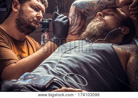 Tattoo artist posing in tatoo salon./Man wearing gloves makes tattoo pictures in tattoo studio.