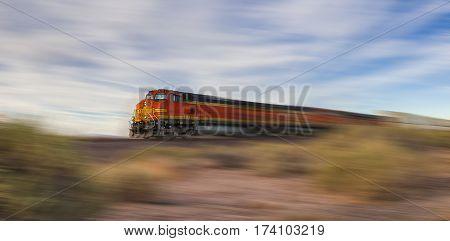 Freight train ride at high speed through the desert