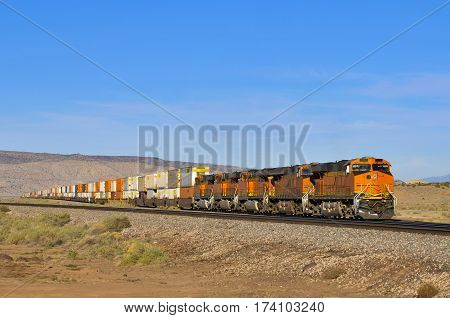 freight train with four locomotives and waggons full of containers in the desert Arizona USA