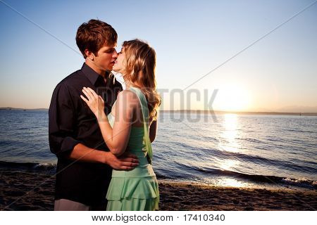 A romantic caucasian couple in love kissing on the beach