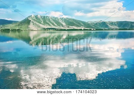 Scenic landscape with lake Orestiada and the reflection of green mountains and white clouds in the blue water. Greece Macedonia Kastoria