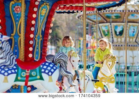 Two blond-haired little friends in jeans and bright windbreakers having fun on colorful carousel
