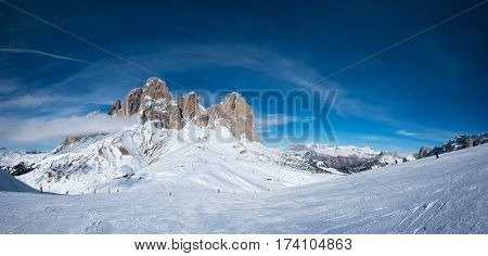 Panoramaof a ski resort piste with people skiing in Dolomites in Italy