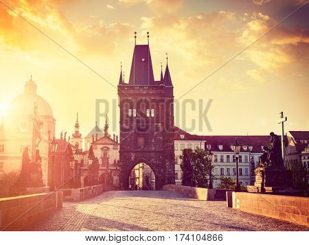 Vintage retro hipster style travel image of Charles bridge tower in Prague on sunrise, Czech Republic. With lens flare and light leak