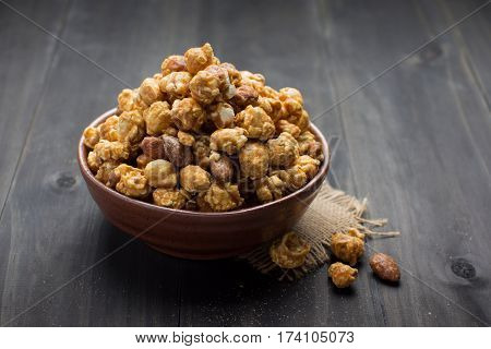 Caramel popcorn in ceramic bowl on wood table