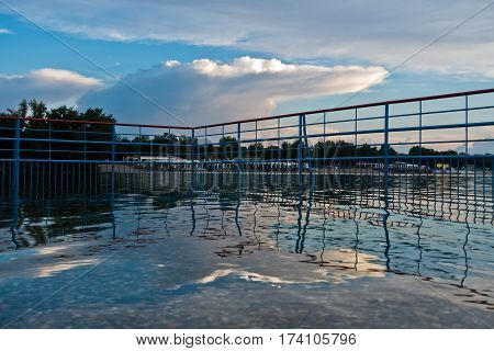 Reflection of picturesque and coloful clouds in a water of Ada lake, Belgrade Serbia