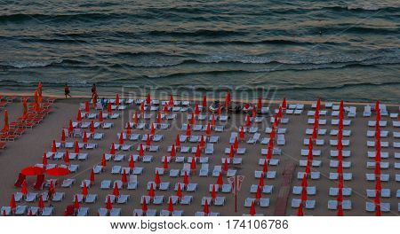 a lot of sun loungers with parasols on the beach.