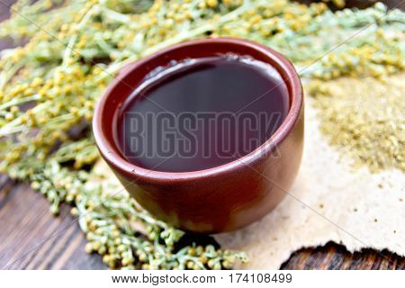 Tea With Wormwood In Clay Cup On Dark Board