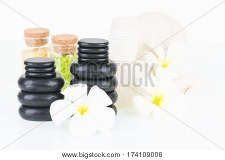 Spa with herbal compress balls, hot stones, bath salt and flowers on white background