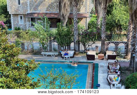 Camyuva Kemer Antalya Turkey - 29 august 2014: The guests of a small hotel relax in the open air near a swimming pool.