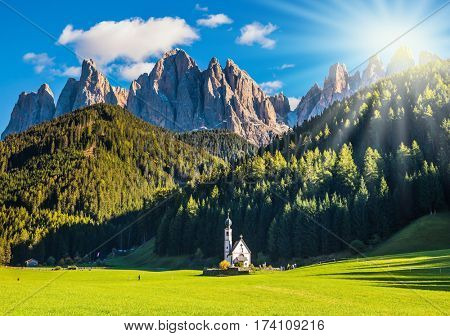 The concept of eco-tourism in Alpine meadows. The morning sun illuminates green valley and church of Santa Magdalena in the Dolomites