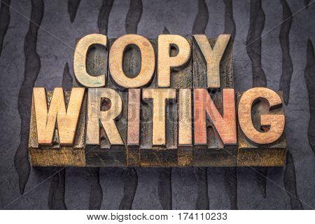 copywriting, word abstract in vintage letterpress wood type blocks against black lokta paper