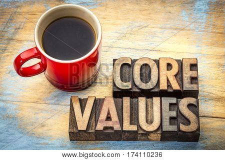 core values  banner  - word abstract in vintage letterpress wood type blocks  against grunge wood with a cup of coffee