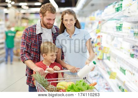 Pretty young woman in blue polo T-shirt posing for camera with wide smile and holding milk bottle in hand while her family looking away