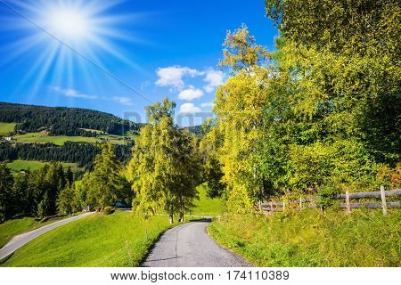 The concept of eco-tourism in Alpine meadows. The sun illuminates rural farm and green alpine valley in the Dolomites. Rural dirt road