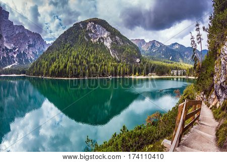 Magnificent Alpine lake Lago di Braies. Walking trail around the lake is fenced with wooden railings. The concept of environmental and hiking