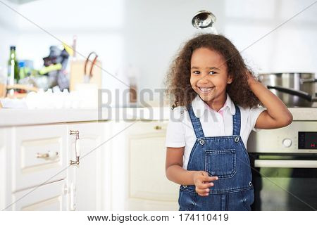 Cute little girl in denim jumpsuit standing next to kitchen oven and looking at camera with toothy smile, waist-up portrait