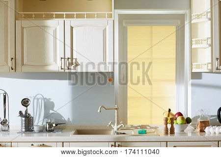 Interior of lovely beige kitchen in classic style: sink with unusual tap, wooden cupboards hanging on walls, cooking utensils and products lying on stone countertop