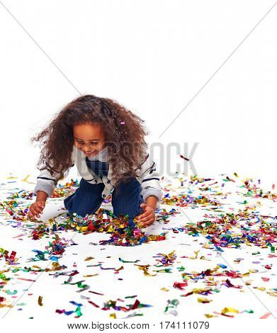 Studio portrait of little African girl with big curly hair crawling on her knees gathering pile of bright foil confetti laughing, ready to toss it up again