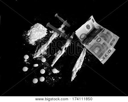 Injection syringe on cocaine drug powder lines, cocaine pile and pills and euro money bills on black background in black and white colors