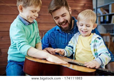 Young bearded father having fun with his sons: little boys with smiles on their faces tapping rhythm on acoustic guitar while their parent looking at them joyfully