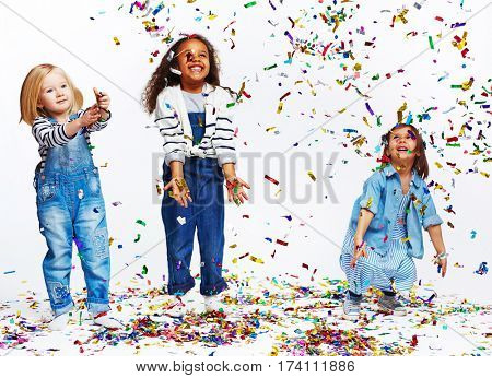 Studio portrait of children against white background: three joyous little girls all dressed in blue jeans clothes having fun tossing big foil confetti in the air