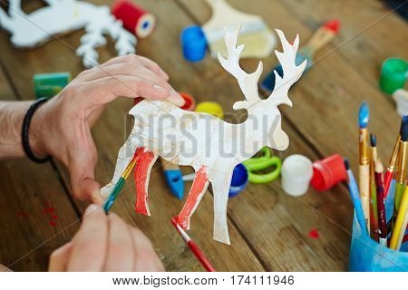 Close-up shot of adult hands holding wooden toy deer and painting it in red, brushes, gouache, scissors laid on table