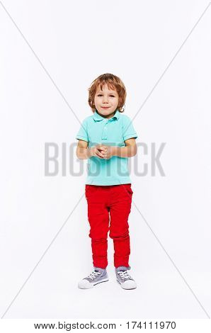 Full body shot of shy little boy dressed in bright colorful clothes standing smiling and twiddling hands against white background