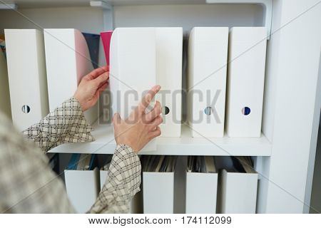 Front view of unrecognizable businesswoman taking white folder from shelf of documentation case in office