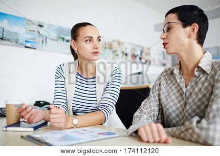 Portrait of two businesswomen, one mature and one young, sitting at desk together in modern office, discussing something