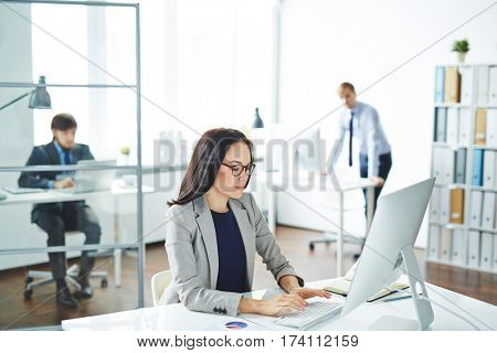Several business people busy working in modern office at desks with computers, focus on young asian woman in front typing something