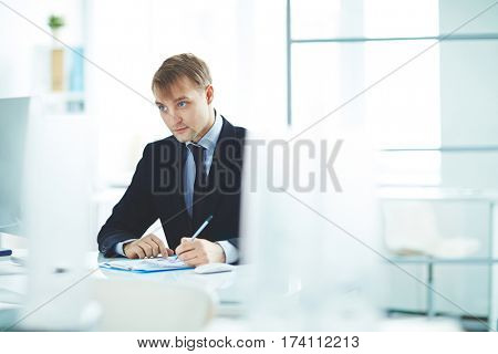 Portrait of successful young business analyst busy working alone in modern office, checking statistics report with graphs and looking at computer screen while sitting at desk