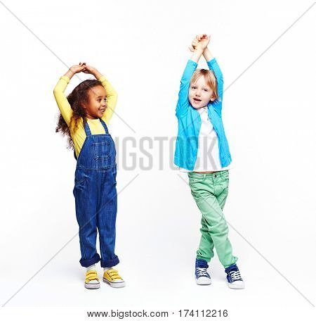 Studio portrait of children against white background:  full body shot of two active kids, African girl and blond boy, doing funny poses with hands up, girl mimicking the boy