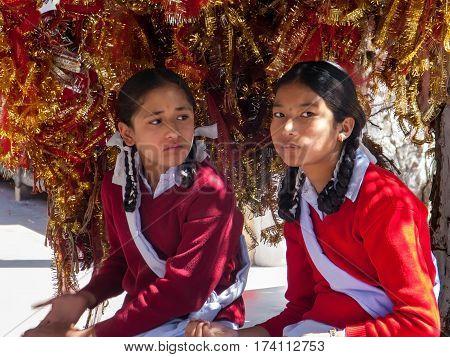 SHIMLA, INDIA. 8 Jun 2009: Daily way of life. Little Indian schoolgirls in traditional school uniforms at a Hindu Temple in the Himalayas. Shimla, Himachal Pradesh, India