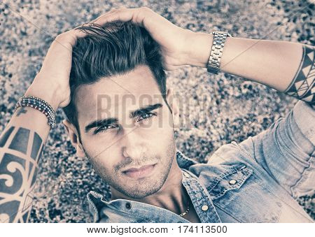 Handsome young, man in denim shirt with tattoos on arms lying in pose on gravel and looking at camera