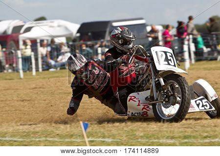 SWINGFIELD, UK - AUGUST 18: One of the leading sidecar teams reaches the apex of the top corner on the circuit the during the Longtrack World Championships on August 18, 2013 in Swingfield