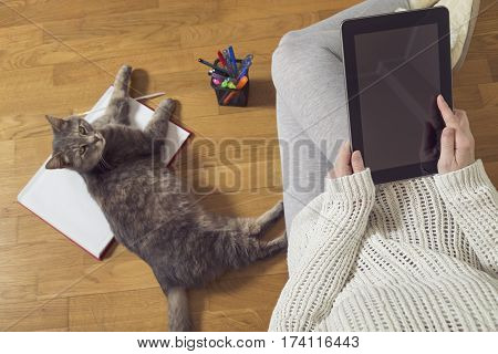 Top view of a woman sitting on the floor holding a tablet computer and working at home with cup of coffee planner and a cat assistant. Selective focus