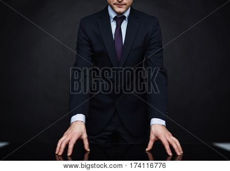 Closeup portrait of unrecognizable authority figure wearing business suit standing leaning on table in powerful pose against black background